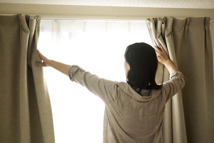 カーテン開ける女性