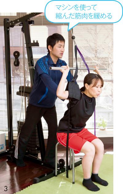3.棒を引き上 げる動きをしながら、菅野さんが背中を押 し、大胸筋をストレッチ。猫背改善効果大。