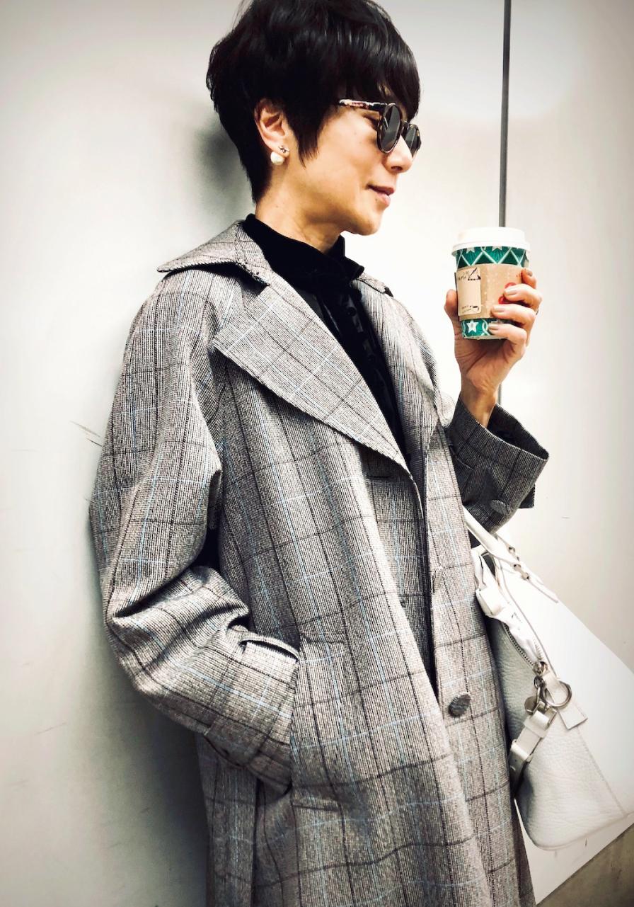 黒田知永子さん 薄手のチェックコートに黒のインナーと白のバッグ