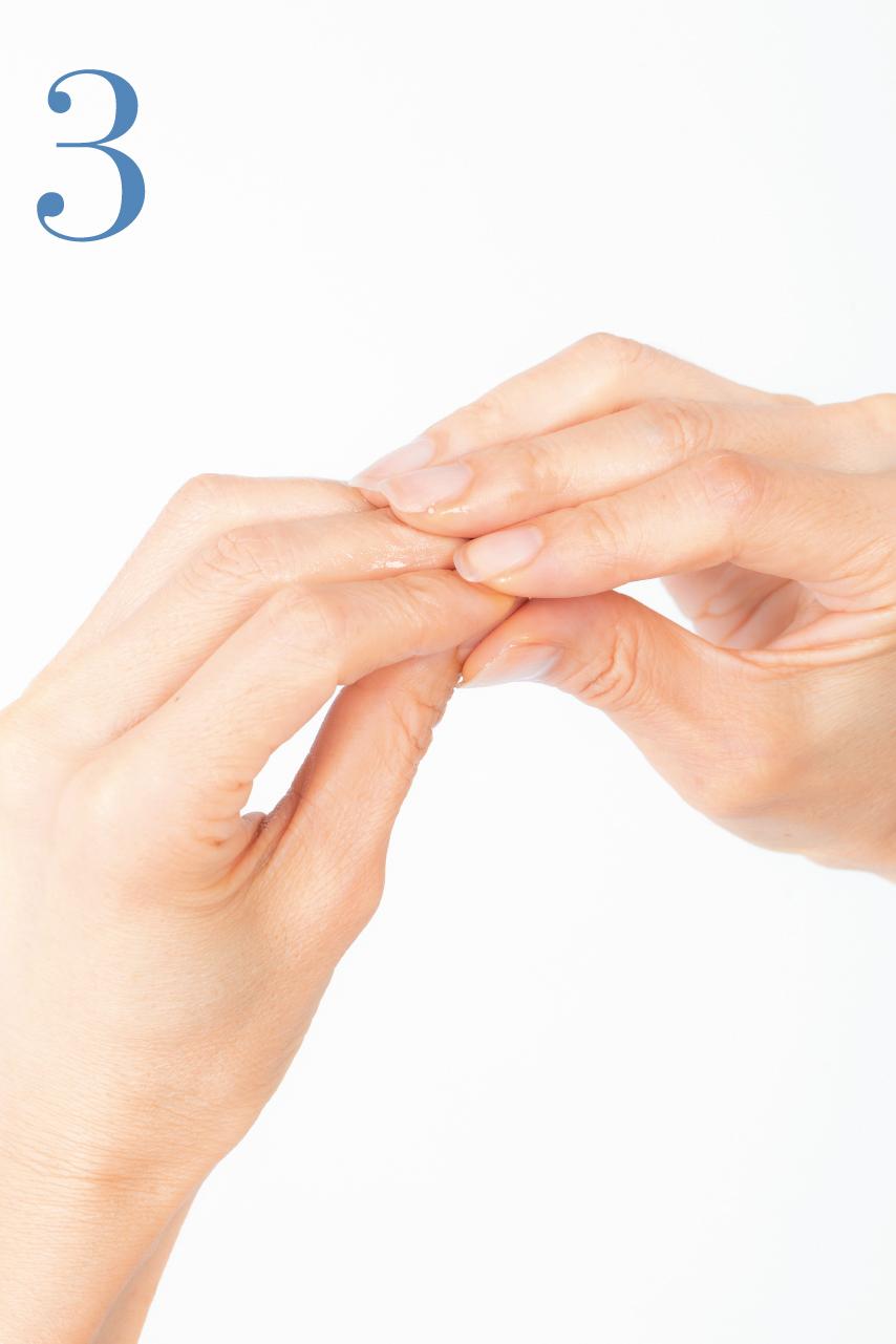 指先を反対の指でもみ込むようにしてオイルを爪全体になじませます。反対の手も同様に