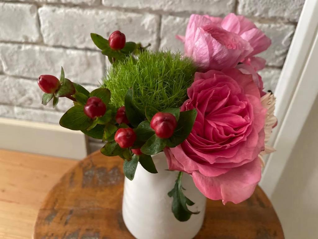 ピッチャーに活けたバラやラナンキュラス