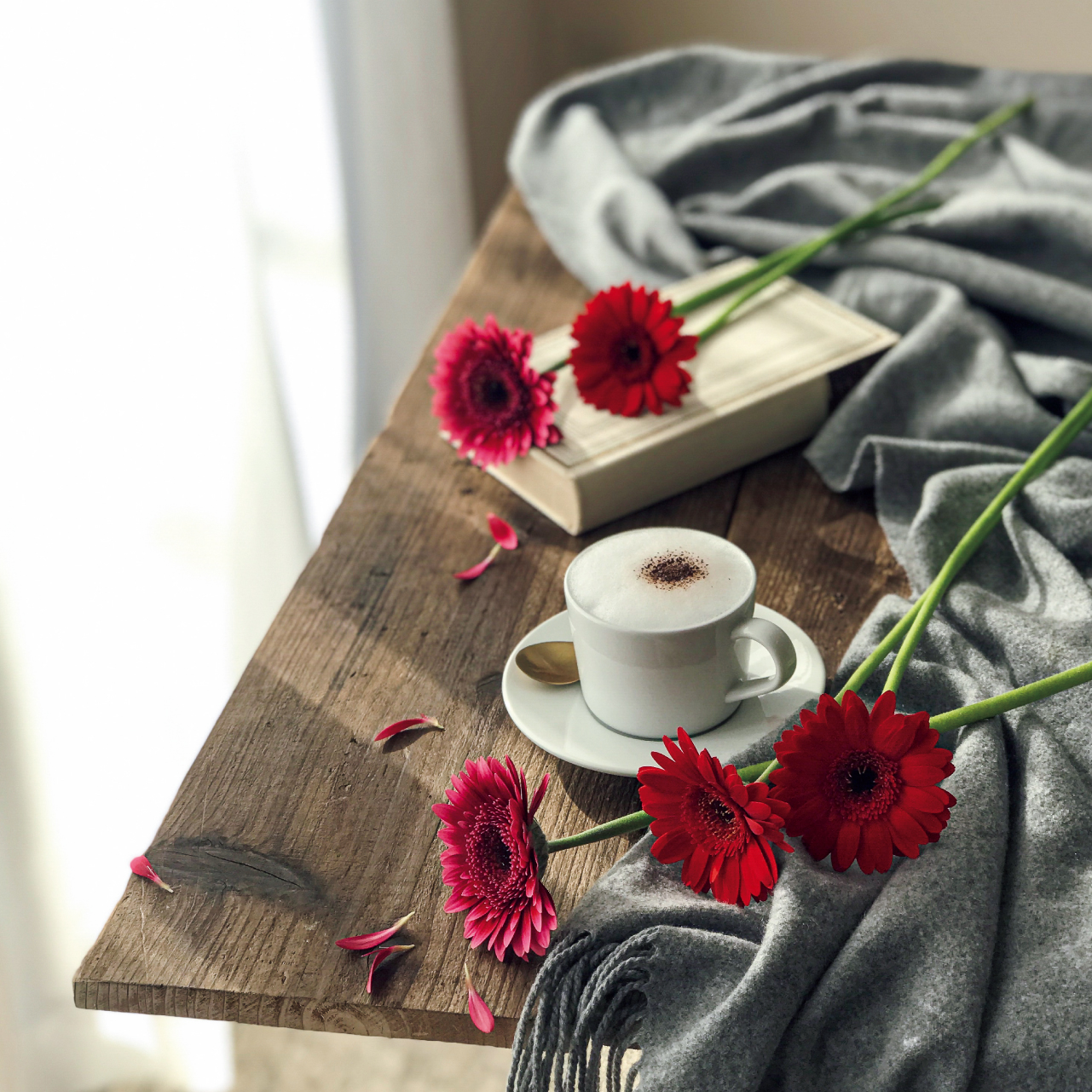 テーブルに飲み物と花と本が置かれたイメージ画像