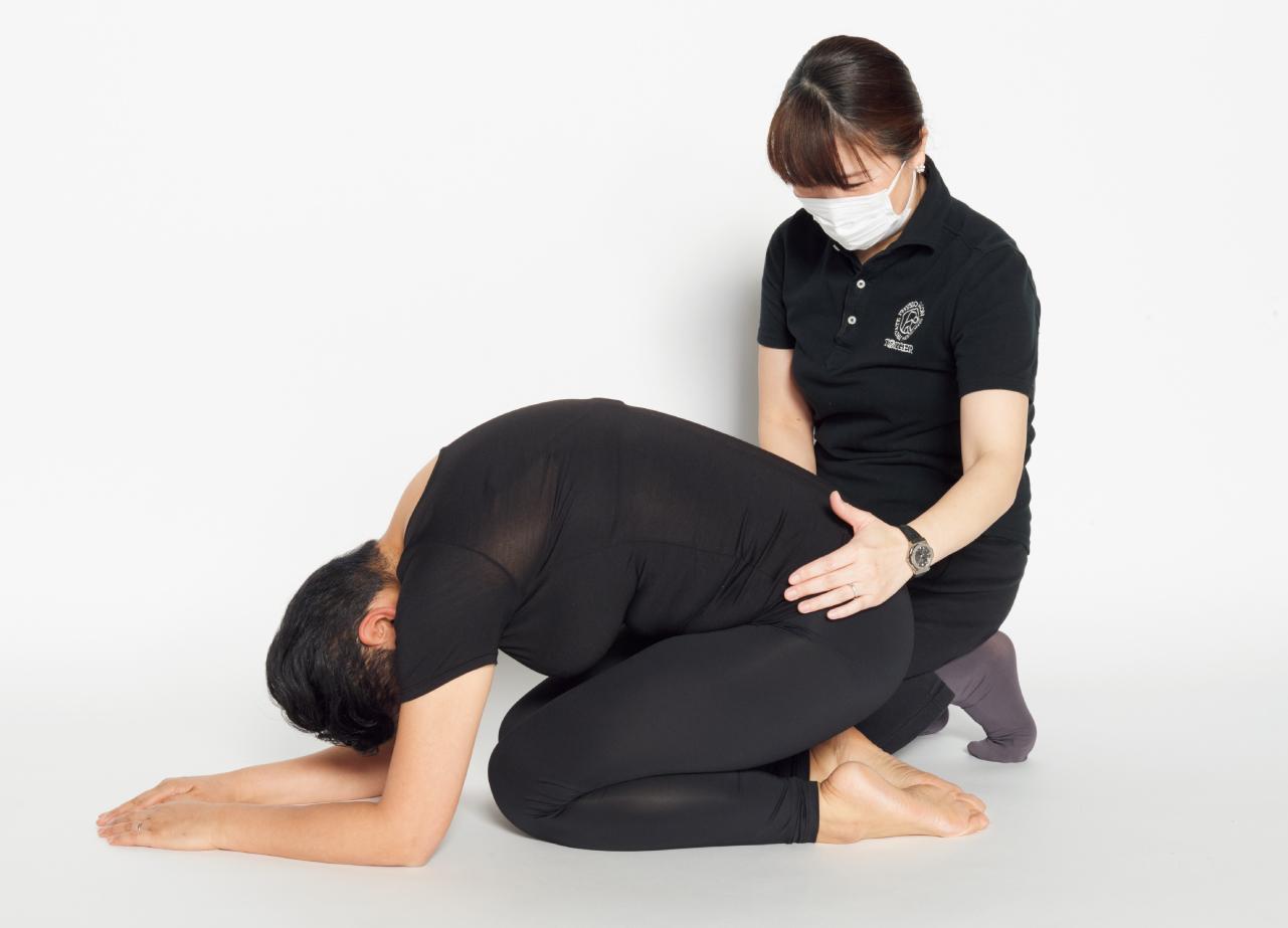 背中を丸める呼吸の練習をするA子さん